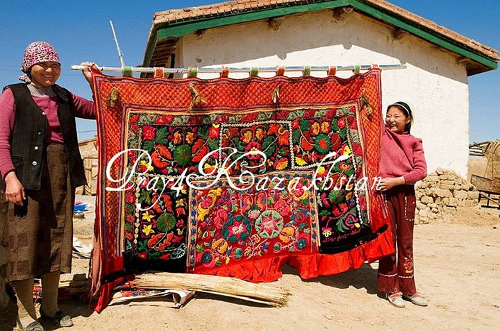 In the rural countryside, Kazakh women hold up an exquisitely ornate tapestry. H…